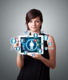 Jeune femme tenant le comprimé avec les icônes sociales de réseau Photo libre de droits