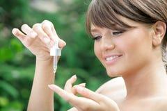 Jeune femme tenant le compte-gouttes avec l'huile essentielle photo libre de droits
