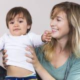 Jeune femme tenant le fils sur des bras photo stock