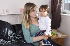 Jeune femme tenant le fils sur des bras image stock