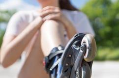 Jeune femme tenant le genou douloureux après être tombé vers le bas photographie stock libre de droits
