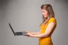 Jeune femme tenant le laptot moderne Image libre de droits