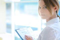 Jeune femme tenant le mur proche dans le bureau Photo libre de droits