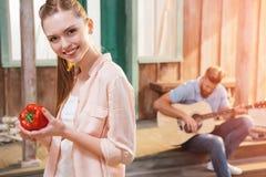 Jeune femme tenant le poivre frais tandis qu'homme jouant la guitare sur le porche Images stock