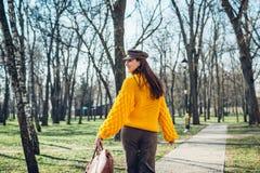 Jeune femme tenant le sac à main élégant et utilisant le chandail jaune Vêtements et accessoires femelles de ressort Mode images libres de droits