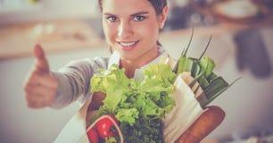 Jeune femme tenant le sac d'épicerie avec des légumes et montrant correct photographie stock