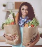 Jeune femme tenant le sac d'épicerie avec des légumes Position dans la cuisine Photographie stock libre de droits