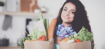 Jeune femme tenant le sac d'épicerie avec des légumes Position dans la cuisine Images stock