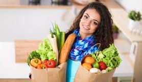 Jeune femme tenant le sac d'épicerie avec des légumes se tenant dans la cuisine Photo libre de droits