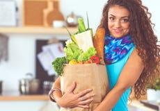 Jeune femme tenant le sac d'épicerie avec des légumes se tenant dans la cuisine images libres de droits
