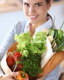Jeune femme tenant le sac d'épicerie avec des légumes se tenant dans la cuisine Photos stock