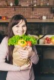 Jeune femme tenant le sac d'épicerie avec des légumes se tenant dans la cuisine Image libre de droits