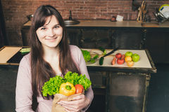 Jeune femme tenant le sac d'épicerie avec des légumes se tenant dans la cuisine Images stock