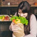 Jeune femme tenant le sac d'épicerie avec des légumes se tenant dans la cuisine Photographie stock libre de droits