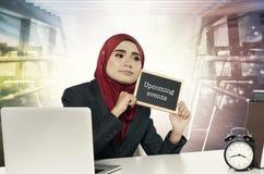 Jeune femme tenant le tableau avec des événements prochains de mot au-dessus de fond abstrait Photographie stock libre de droits