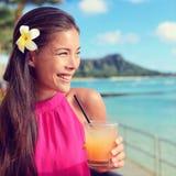 Jeune femme tenant le verre de cocktail à la barre de plage image stock