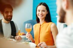 Jeune femme tenant le verre tout en mangeant avec des amis Image stock