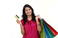 Jeune femme tenant les sacs à provisions et la carte de crédit photos stock