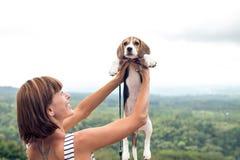 Jeune femme tenant son chien de briquet de chiot en nature d'île tropicale de Bali, Indonésie Photos stock