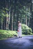 Jeune femme tenant son chien de briquet de chiot en nature d'île tropicale de Bali, Indonésie Images libres de droits