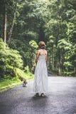 Jeune femme tenant son chien de briquet de chiot en nature d'île tropicale de Bali, Indonésie Images stock