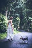 Jeune femme tenant son chien de briquet de chiot en nature d'île tropicale de Bali, Indonésie Image stock