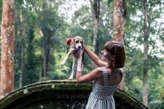 Jeune femme tenant son chien de briquet de chiot en nature d'île tropicale de Bali, Indonésie Photographie stock libre de droits