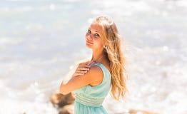 Jeune femme tenant tout près la mer de plage dans la robe bleue Image stock