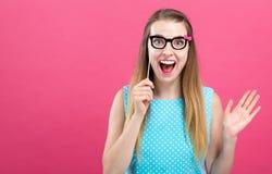 Jeune femme tenant un bâton de papier de partie en verre photo stock