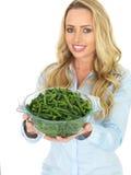 Jeune femme tenant un bol de haricots verts fraîchement cuits Image libre de droits