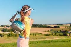 Jeune femme tenant un club de conducteur pendant l'oscillation de golf au commencer Photographie stock