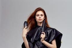 Jeune femme tenant un fer de bordage, un coiffeur images libres de droits