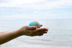 Jeune femme tenant un globe dans des ses mains Photos stock