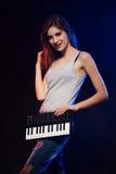 Jeune femme tenant un mini piano électronique Images stock