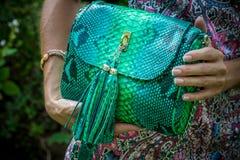 Jeune femme tenant un sac à main fait main de luxe de python de peau de serpent Jour ensoleillé Embrayage cher Fermez-vous des ma Image libre de droits
