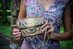 Jeune femme tenant un sac à main fait main de luxe de python de peau de serpent Jour ensoleillé Embrayage cher Fermez-vous des ma Image stock