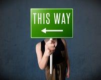 Jeune femme tenant un signal de direction Image libre de droits