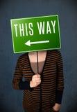 Jeune femme tenant un signal de direction Photo libre de droits