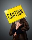 Jeune femme tenant un signe de précaution Photographie stock libre de droits