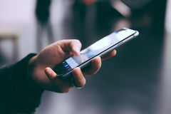 Jeune femme tenant un smartphone, vue de côté Images stock