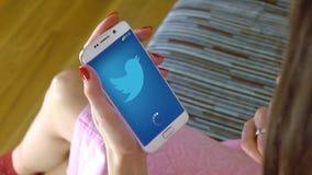 Jeune femme tenant un téléphone portable avec le Twitter APP mobile de chargement Agrafe conceptuelle de l'éditorial 4K banque de vidéos