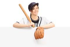 Jeune femme tenant une batte de baseball derrière le panneau Images libres de droits