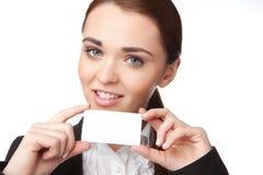 Jeune femme tenant une carte de visite professionnelle de visite sur le fond blanc Photos stock