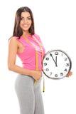 Jeune femme tenant une grande horloge murale Images stock