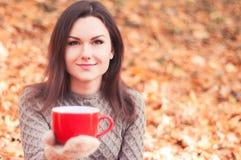 Jeune femme tenant une grande tasse rouge Image libre de droits