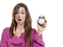 Jeune femme tenant une main sur sa bouche, et tenant une montre à six horloges d'o Photo stock