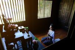 Jeune femme thaïlandaise asiatique priant Bouddha avec le lotus dans la chambre Bouddha photos stock