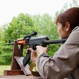 Jeune femme tirant une arme automatique photos stock