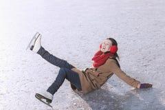 Jeune femme tombant tandis que patinage de glace Photographie stock libre de droits