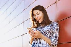Jeune femme ?tonn?e ? l'aide du t?l?phone intelligent dehors Croissant doux et une cuvette de caf? ? l'arri?re-plan image libre de droits